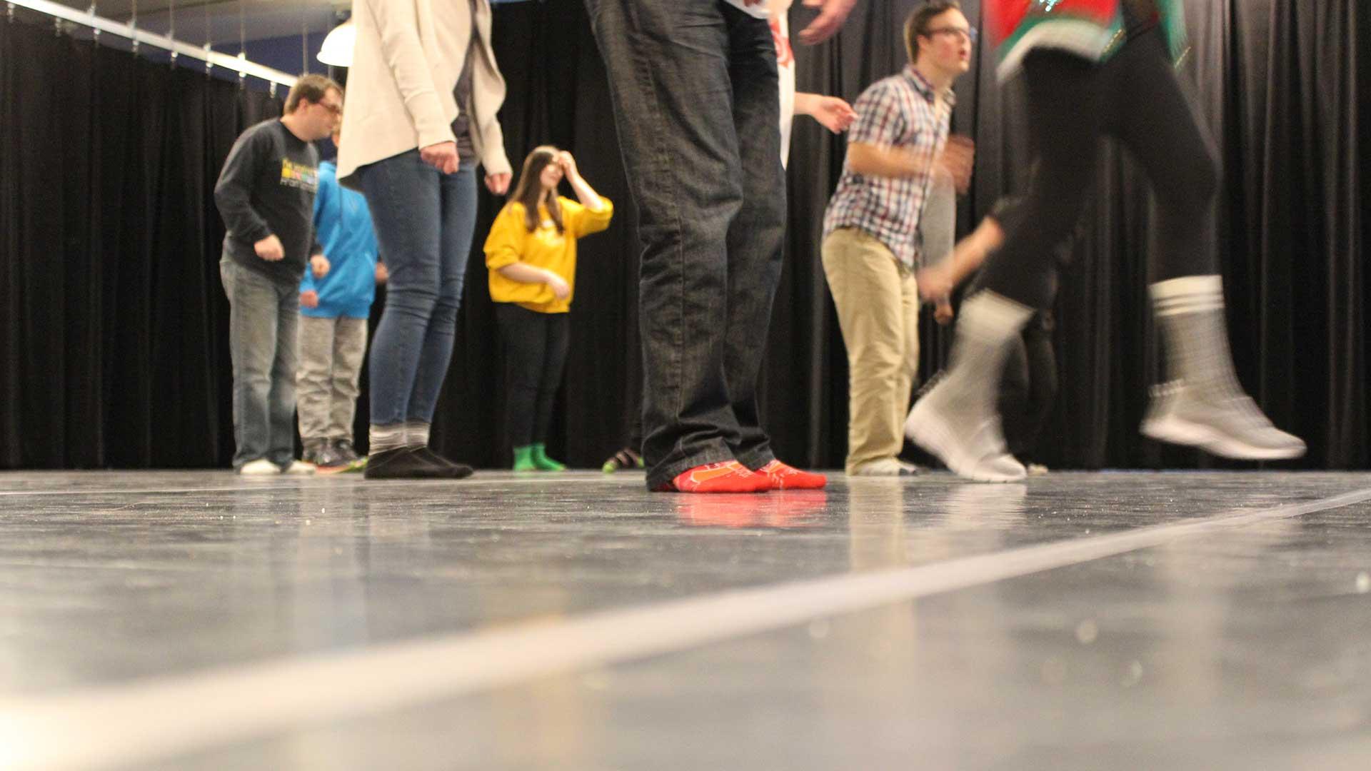 Socked feet and legs on dance floor