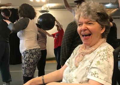 Laughing woman with wheelchair, dance class in background