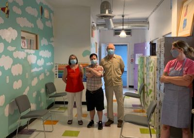 Masked artist and two family members in hallway with masked H'art staff