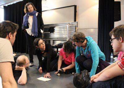 Creative team discusses while sitting on theatre floor