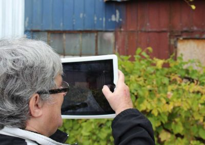 H'art artist taking a photo of a barn with iPad