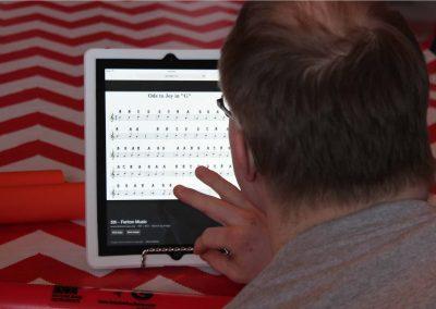 H'art artist using an iPad to read sheet music