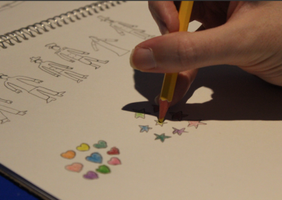 Hand holding yellow pencil crayon filling in a star under sketches of community helpers