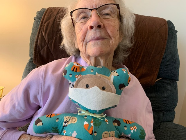 June holds masked bear while smiling